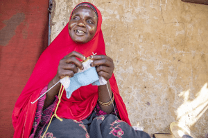 Jummai has worked multiple, varied jobs to support her family. Today, she's running a livestock business with the local Village Savings and Loan Association, along a knitting business. Her current project is a cap for a one-month-old newborn