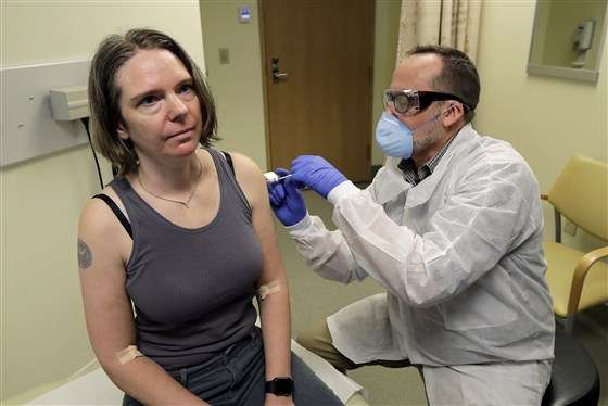 A pharmacist gives Jennifer Haller the first shot in the first-stage safety study clinical trial of a potential vaccine for COVID-19 on Monday at the Kaiser Permanente Washington Health Research Institute in Seattle.Ted S. Warren / AP