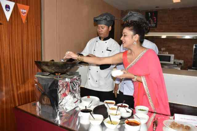 Popular Assamese actress Zerifa Wahid helping one of the chefs at the live display counter during the unveiling of the new menu at Yo China, Guwahati on Thursday
