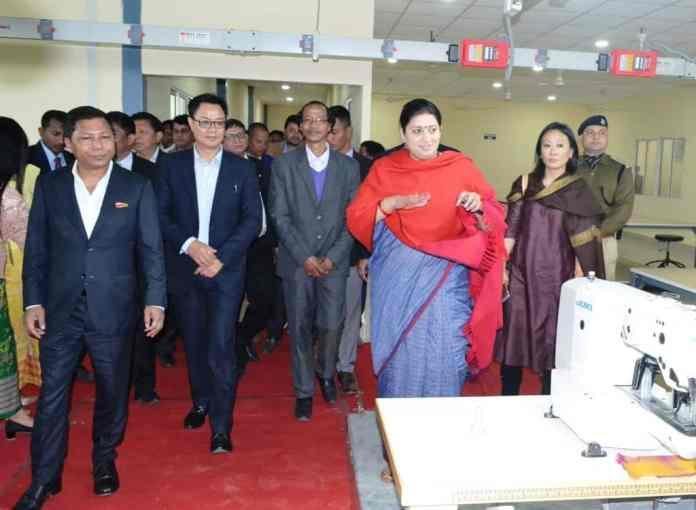 Smriti Irani accompanied by Mukul Sangma and Kiren Rijiju inspects the apparel and garment making centre at Hatisil, Ampati on Monday