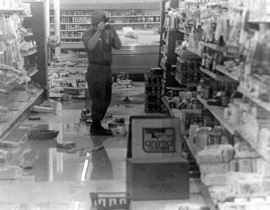 A guardsman takes photos in a looted store. (Credit: State Archives of Florida)