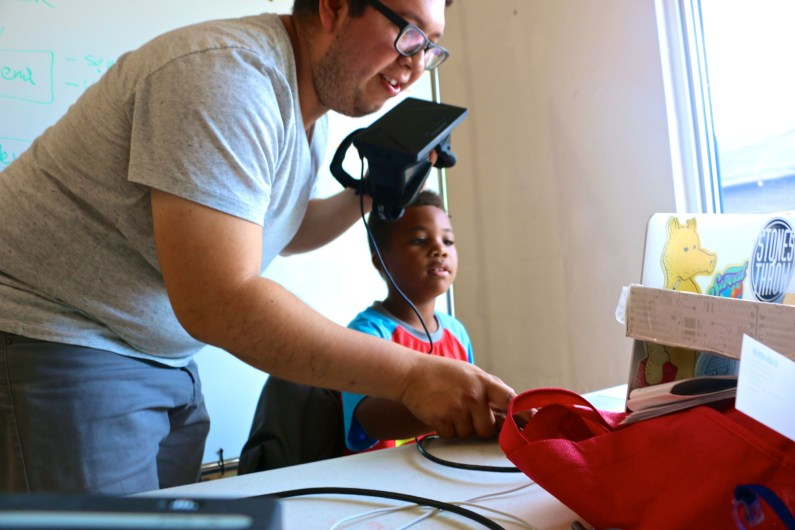 Willie Avendano sets up an Oculus Rift for a student at Wynwood Maker camp. (Wynwood Maker Camp photos)