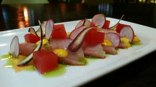 Szechuan cured hamachi sashimi, miso carrot, and compressed melon. (Courtesy of Justin Sherrer)