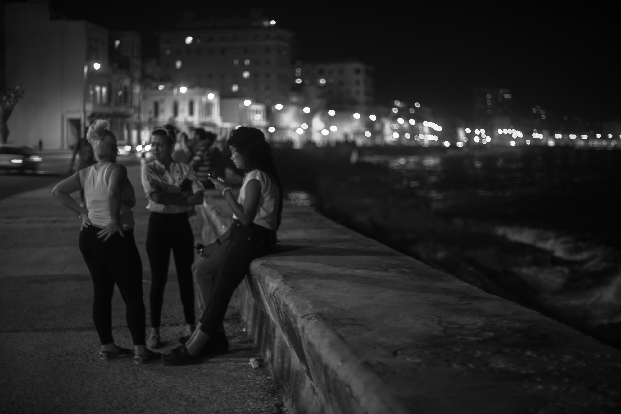 A group of young women hang out on the Malecón.