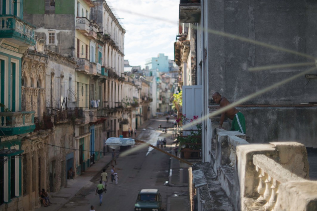 A man chills on his balcony in Old Havana.