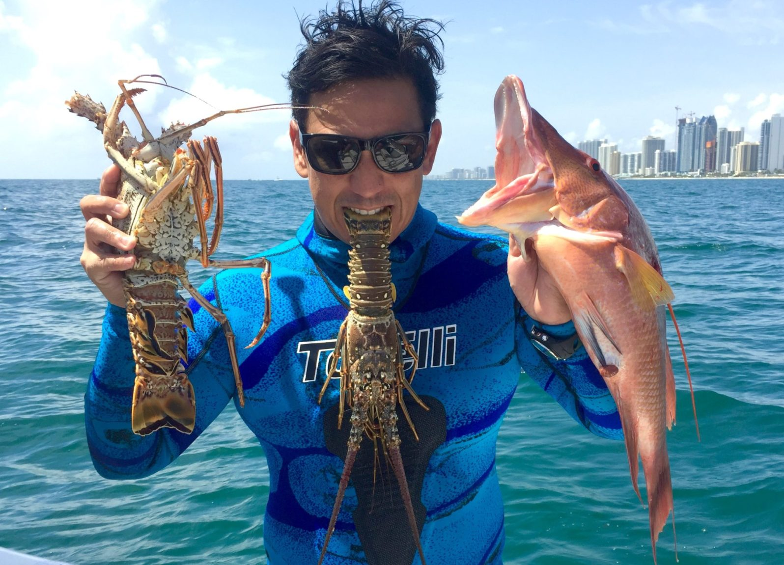 Roy Ferreira with a fresh catch, with Miami in the background. (Photo courtesy of Roy Ferreira)