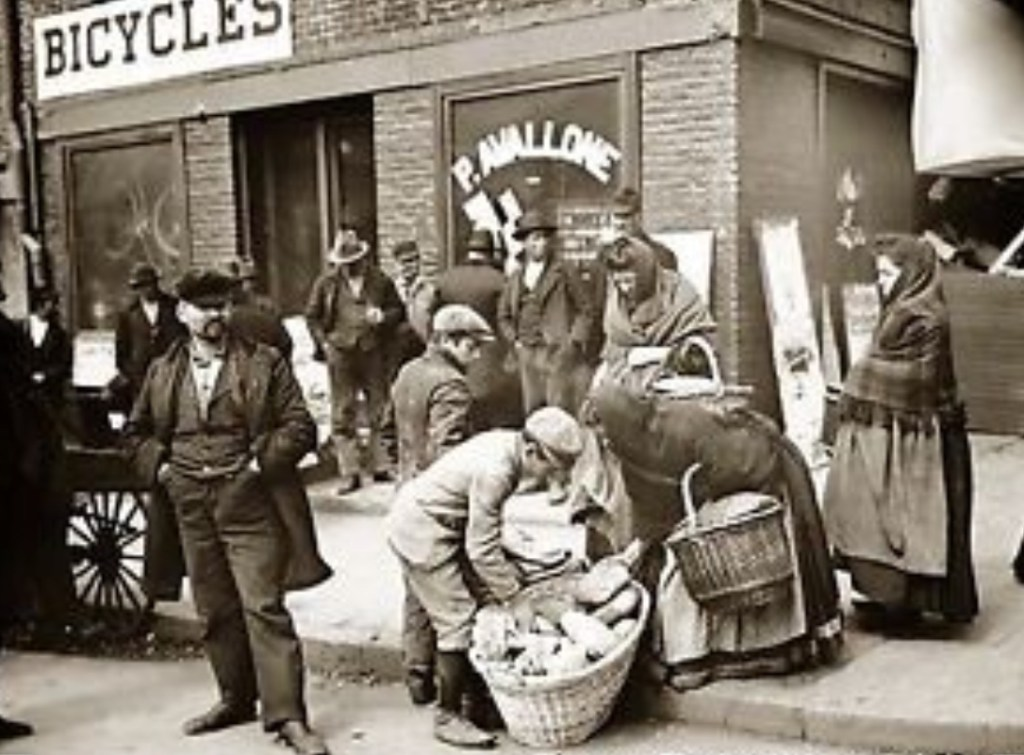 Young Italian teenagers hawking fresh hot loaves of Italian bread on a street in New York's Little Italy. Note the Avallone Bicycle Shop in the background, and the heavily mustached immigrant in the foreground.