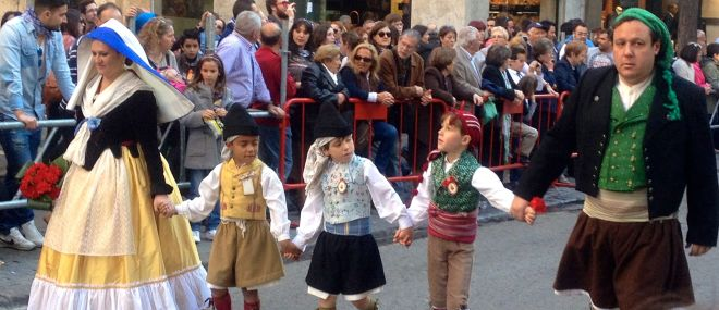 A family in traditional Valencian costume taking flowers to the Virgin Mary during the L'Ofrena de Flors