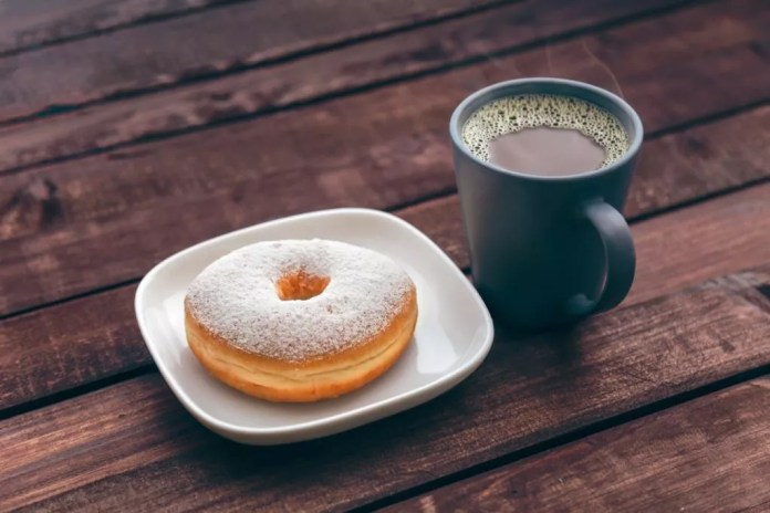 A cup of coffee and powdered sugar doughnut