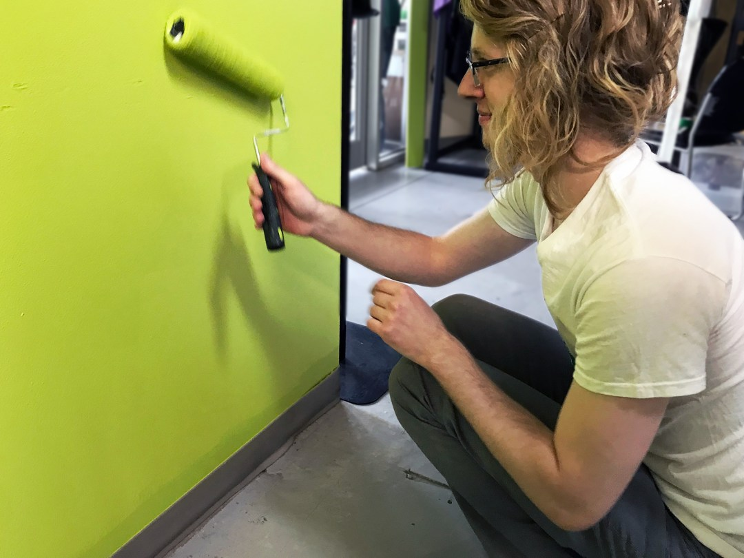 Mitch kneeling down painting a wall bright green with a paint roller
