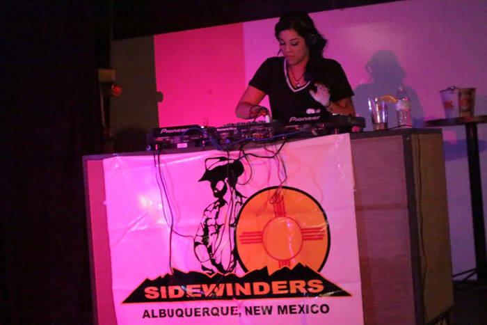 A view of DJ Angel Pitch behind the Sidewinders banner.
