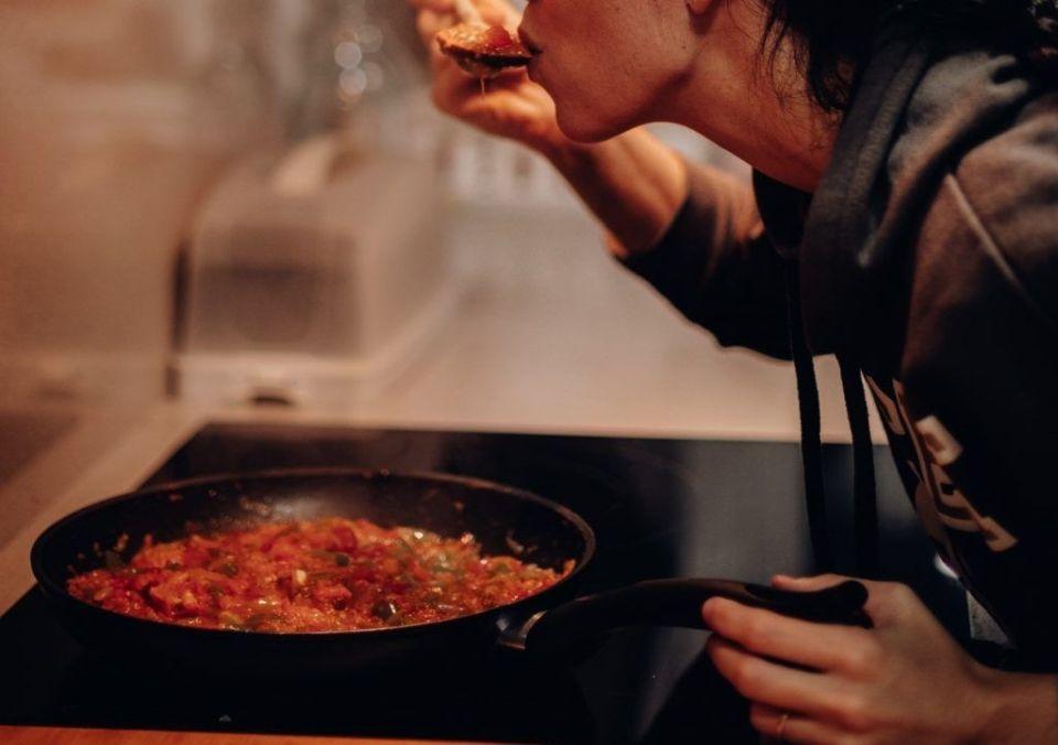 Women Tasting food over pan