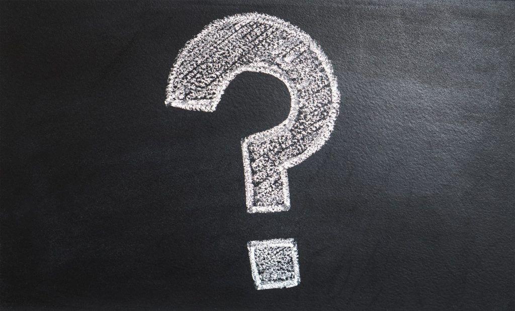 Question mark written on chalkboard with white chalk
