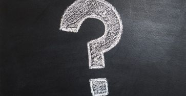 Question mark written on chalkboard with white chalk