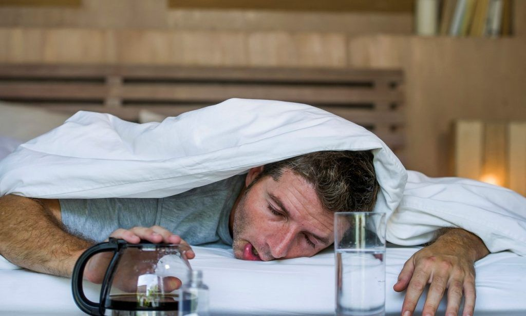 Man in bed with a hangover