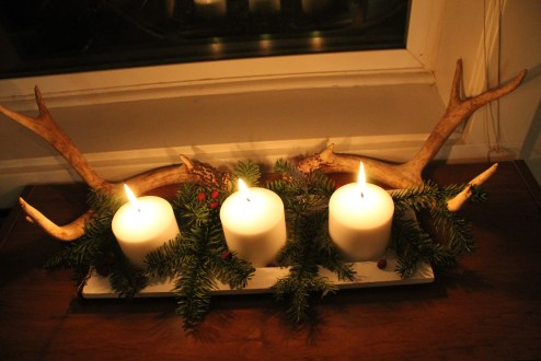 Decorate the top of a bookshelf with candles, greenery from your tree and a pair of antlers (that your dog just happened to drag into the yard!)