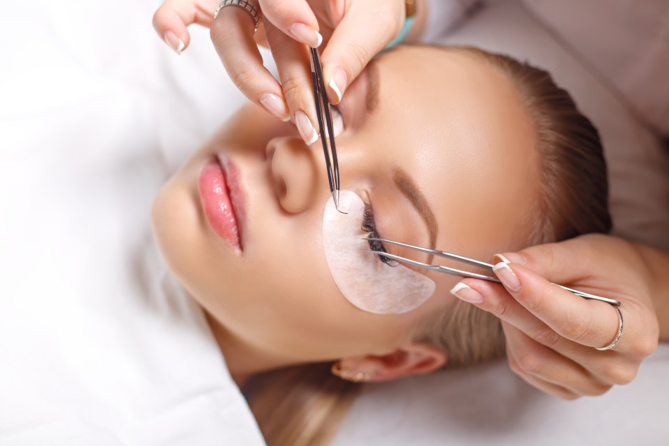 Woman having eyelash extensions applied