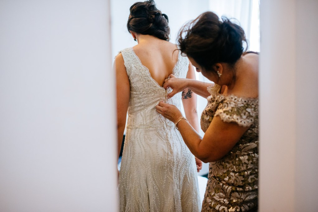 mom sewing bride into dress