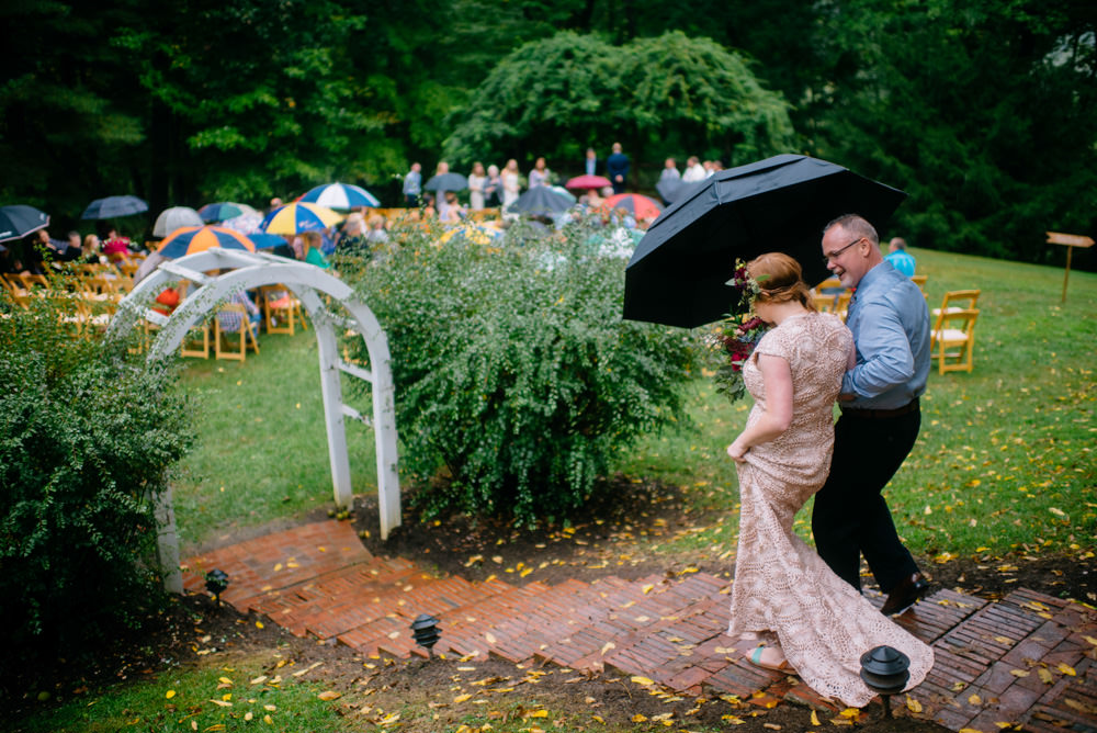 bride and father walking down aislewith umbrella wedding ceremony benedict haid by the oberports