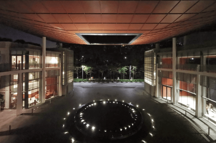 a picture of Yale-NUS Oculus, a driveway with a fountain in the middle, at night