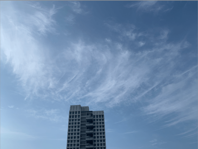 A bottom-up shot of one of Yale-NUS's residential buildings against a blue sky and featherly clouds