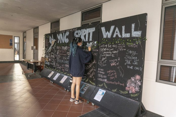A student writing messages on YNC Spirit Wall outside of Saga Dining Hall