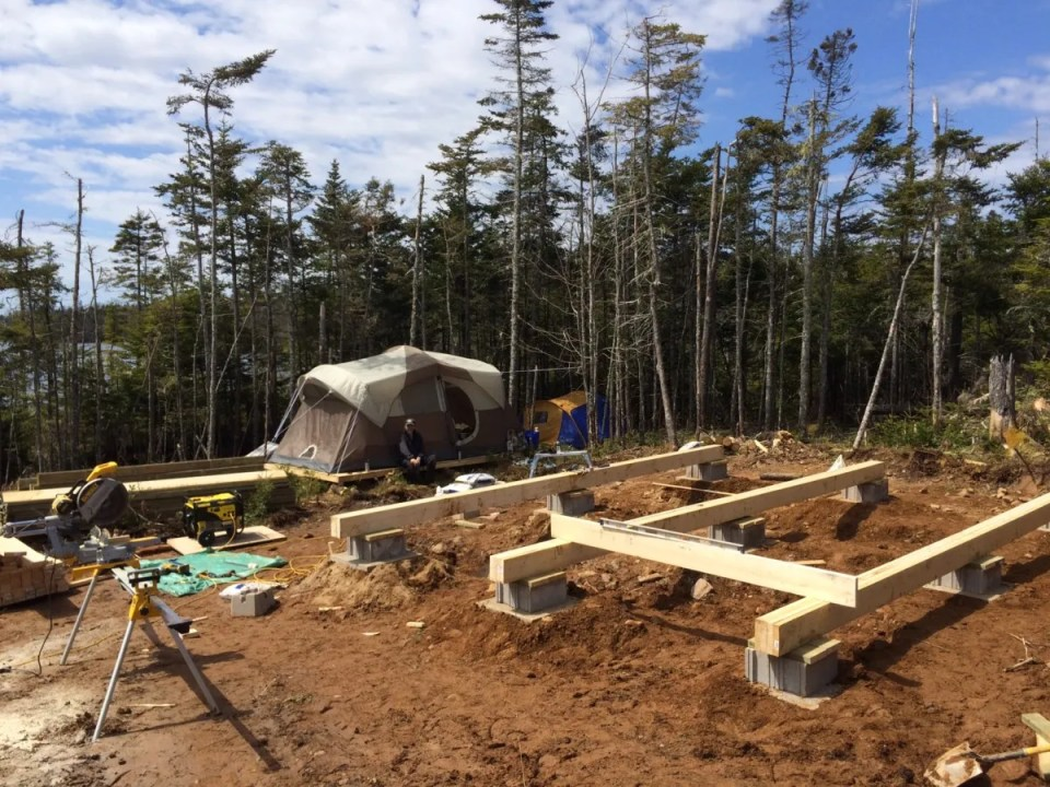 Laying out the beams for the off grid cabin foundation