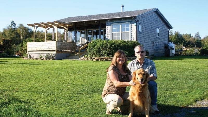Debbie and Mike Cameron pose with their five-year-old golden retriever, Ben, in front of their off-grid home near Pugwash, Nova Scotia.