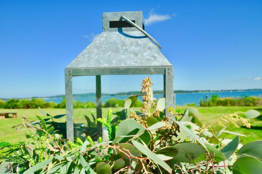 Lantern set in eucalyptus leaves with Peconic Bay and Shelter Island in background.