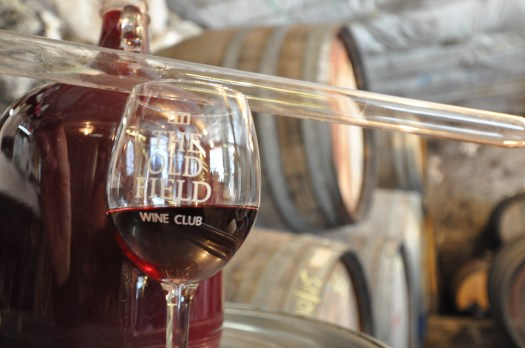 Wine glass with red wine in it in front of barrels