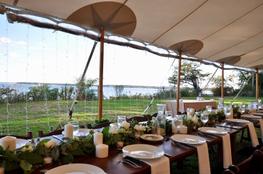 Wooden farm table running horizontally under a Sperry Tent, with table settings and white roses mixed in a greener runner. View is out to the Bay.