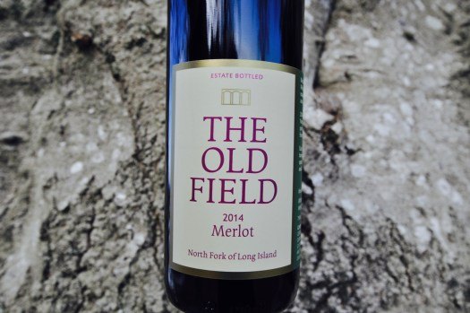 Bottle of 2014 Merlot with bark of tree in background.