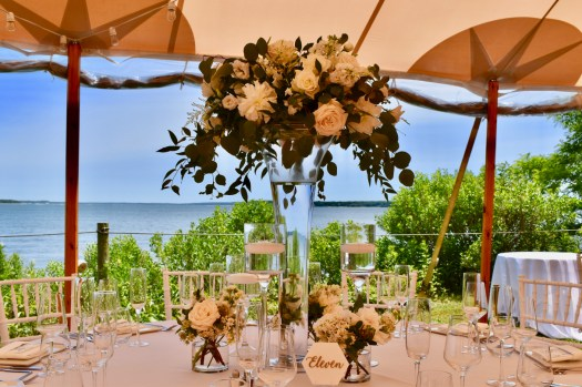 Set table with flowers under tent with water in background