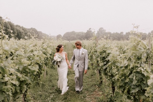 Couple walking hand in hand in vineyards in late June