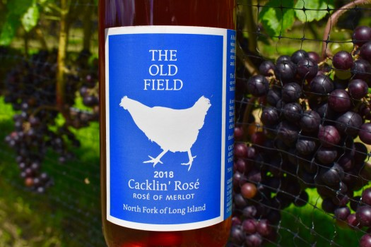Our 2018 Cacklin rose (Rose of Merlot) bottle in front of grapes.