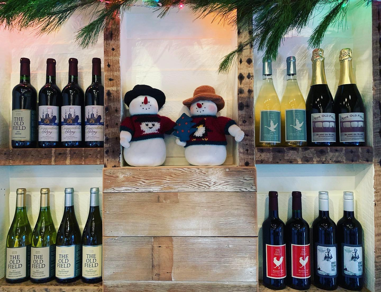 wall with shelving and wine on it. Also some snowmen figures.
