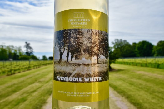 Bottle of Winsome White in front of our dirt road.
