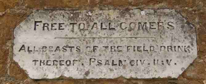 """A stone plaque above a trough in Tysoe. The plaque reads """"Free to all comers - Beasts of the field drinbk thereof. Psalm civ.ii:v"""