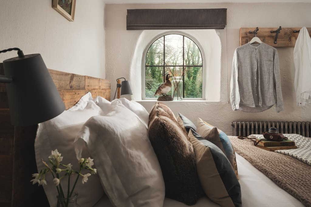 Cosy king size bed wih french linens adorn he master bedroom of this romantic cornish cottage