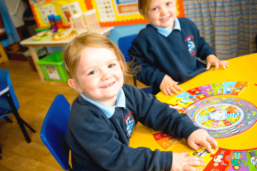 Two pre-school girls playing with alphabet jigsaw on a yellow table, at The Old Station Nursery in Dromore