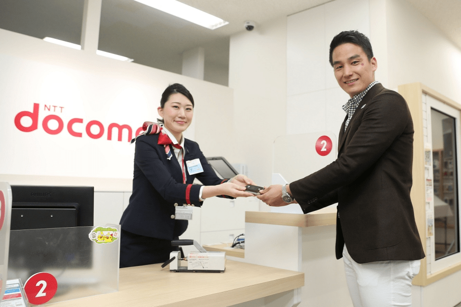 Takeshi Matsuda donating phone for recycling at an NTT-DoCoMo outlet