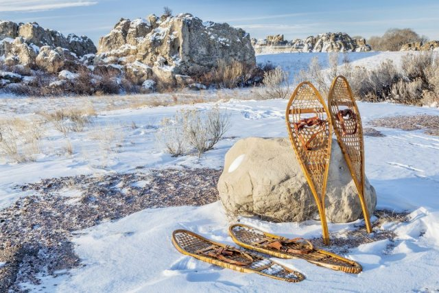 Two pairs of vintage snowshoes propped against a rock.