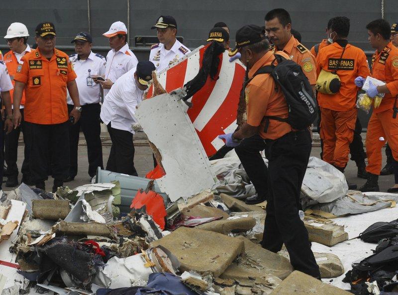 A rescuer inspects a part of Lion Air plane flight JT 610-AP