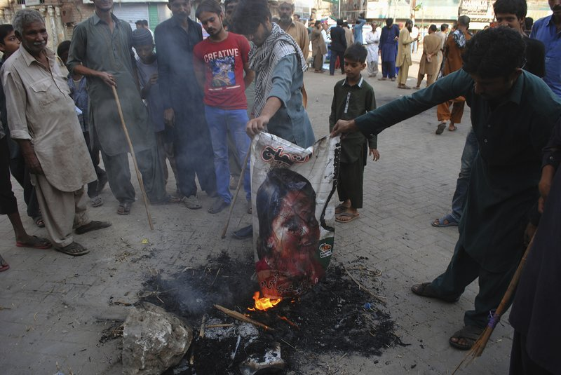 Pakistani protesters burn a poster image of Christian woman Asia Bibi-AP