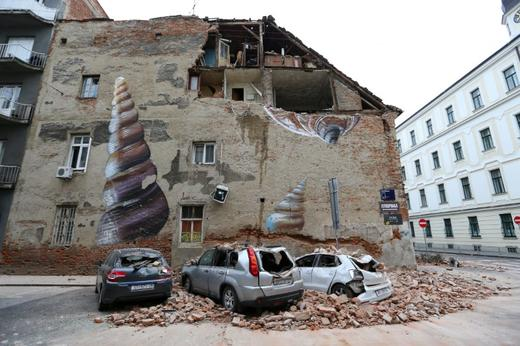 Damaged cars and a partially damaged building are seen following an earthquake, in Zagreb-REUTERS
