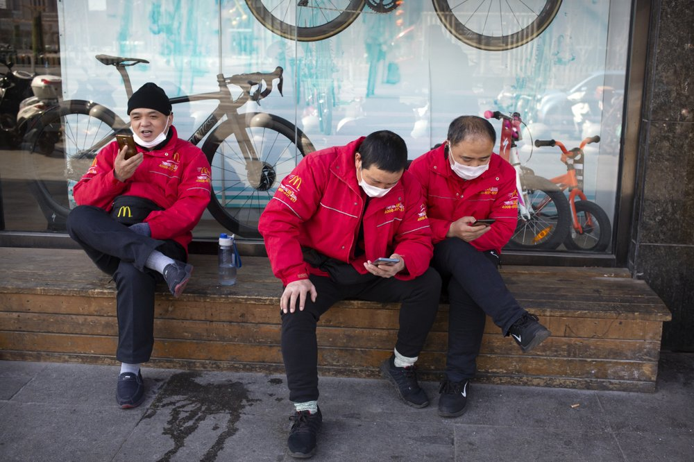 McDonald's deliverymen wear face masks as they wait for orders outside a restaurant in Beijing-AP