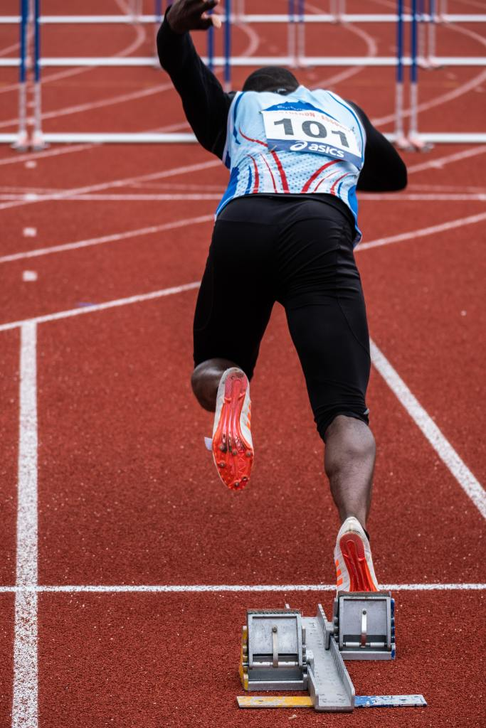 Sprinter bursting out of the blocks on a running track