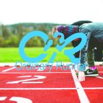 Child and adult lining up on a running track overlaid by the Ordinary Runner logo