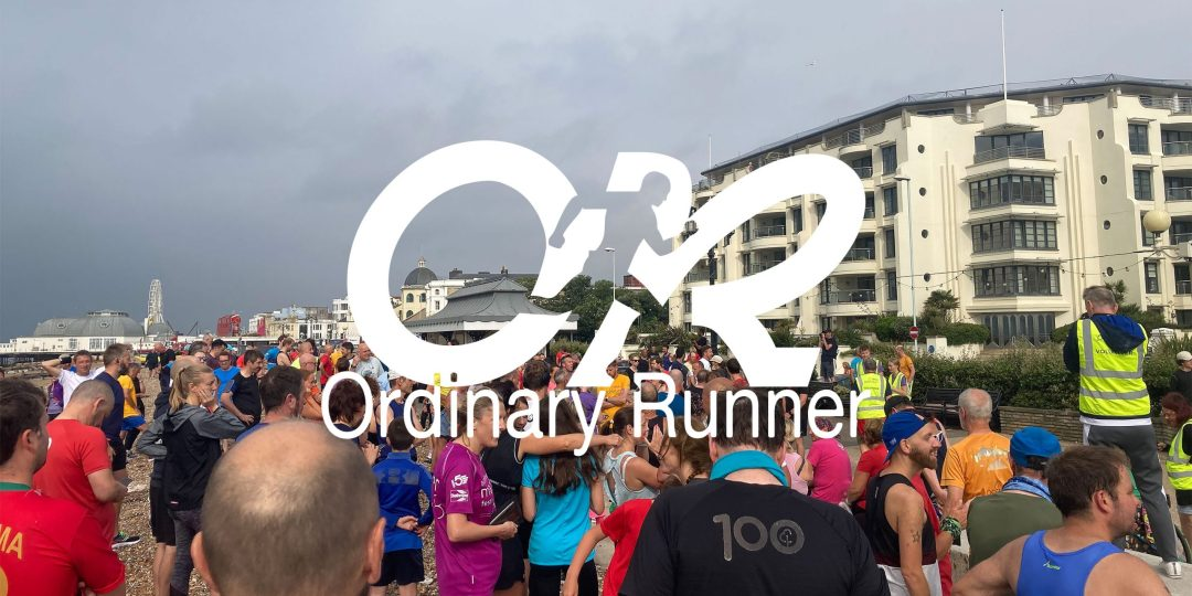 Crowds gather at the start line of Worthing parkrun overlaid by the Ordinary Runner logo