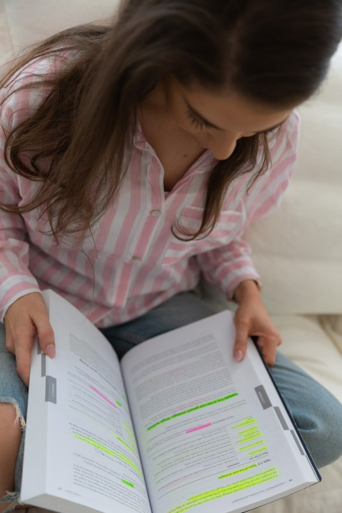 Girl sitting down, reading CPA text book
